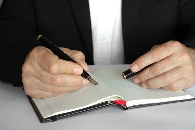 Persona d'affari che scrive con una penna su un blocco note.