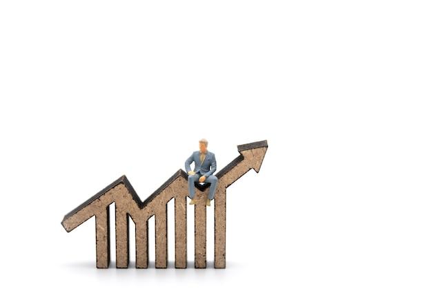 Concetto di affari e pianificazione. primo piano della figura in miniatura dell'uomo d'affari persone sedute su barra di legno e ritaglio di grafico a freccia lineare isolato su sfondo bianco