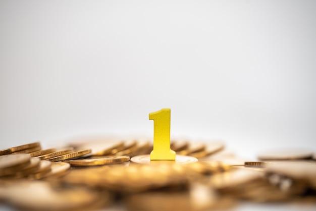 Business, pianificazione e concetto di destinazione. primo piano del numero 1 di legno giallo sulla pila di monete d'oro come con sfondo bianco.