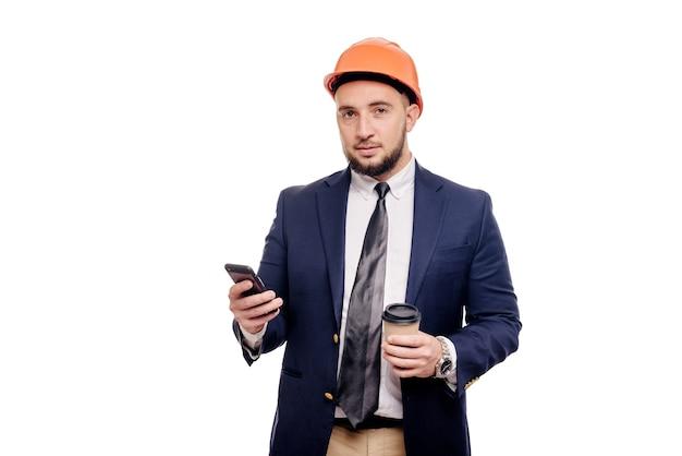 Ritratto di affari di imprenditore e sviluppatore sorpreso, parlando di telefono. uomo d'affari in cappello duro con una tazza di caffè in piedi su sfondo bianco. notizie e concetto di freno del caffè