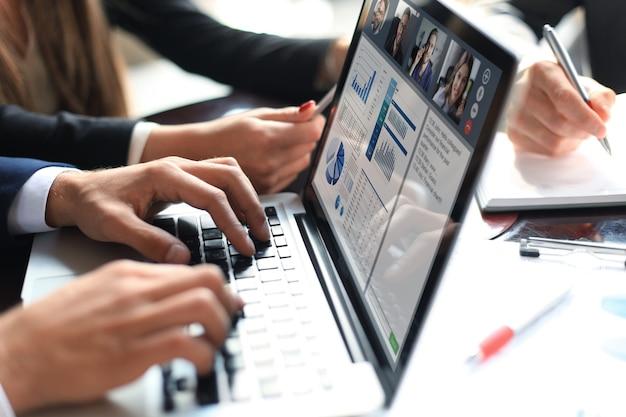 Professionisti aziendali che lavorano insieme alla scrivania dell'ufficio, analizzando le statistiche finanziarie visualizzate sullo schermo del laptop. conferenza di gruppo in webcam con i colleghi sul laptop.
