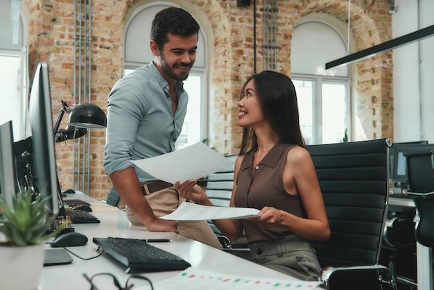 Professionisti aziendali giovane bella donna che mostra alcuni documenti al suo allegro collega maschio
