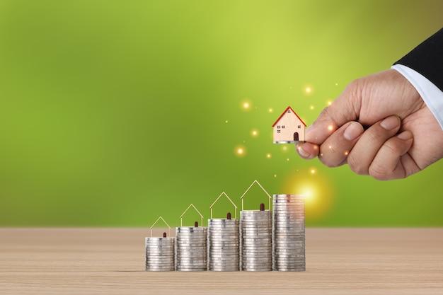 Investimento immobiliare aziendale con la mano dell'uomo d'affari che impila la crescita crescente della moneta con il modello della casa sulla scrivania in legno con sfondo verde per il concetto di pubblicità immobiliare finanziaria