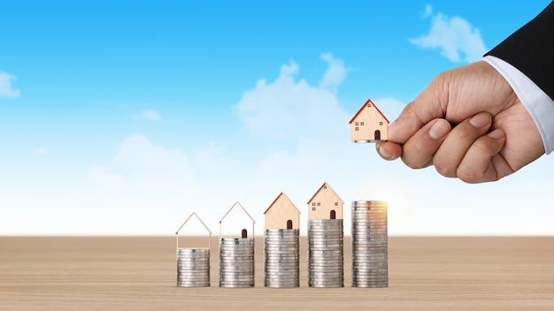 Investimento immobiliare aziendale con la mano dell'uomo d'affari impilando la crescita crescente della moneta con il modello della casa sulla scrivania in legno con lo sfondo del cielo per il concetto di pubblicità immobiliare finanziaria