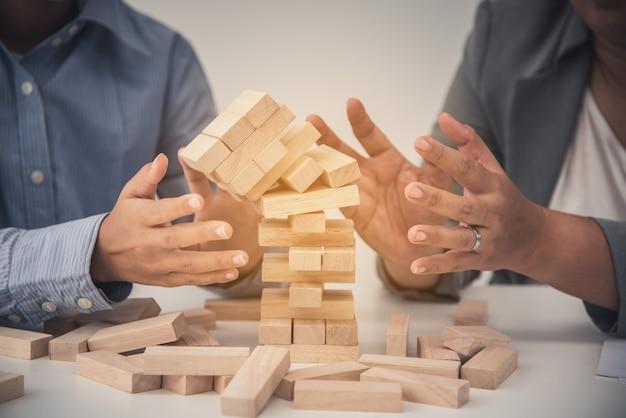 Rischi aziendali nel business. richiede pianificazione la meditazione deve stare attenta nel decidere di ridurre il rischio nel business. mentre il gioco si avvicinava a un blocco di legno dalla torre