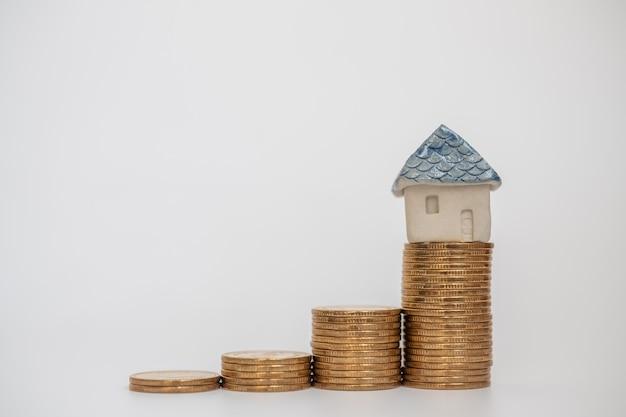 Affari, risparmio e concetto di prestito domestico. primo piano della casa giocattolo in ceramica in cima alla pila di monete d'oro su sfondo bianco.