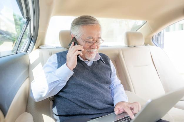 Uomo ricco anziano d'affari giocatore di borsa in tuta che lavora con il computer portatile e utilizza uno smartphone nella sua auto, concetto per il successo aziendale senior