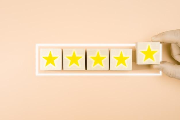 Valutazione del servizio aziendale, concetto di soddisfazione. mano che organizza l'icona della stella simbolo sul blocco cubo di legno