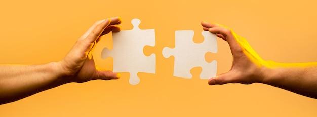 Soluzioni aziendali, successo e concetto di strategia. due mani che cercano di collegare un paio di pezzi di puzzle su sfondo giallo. tenendo puzzle. concetto di lavoro di squadra