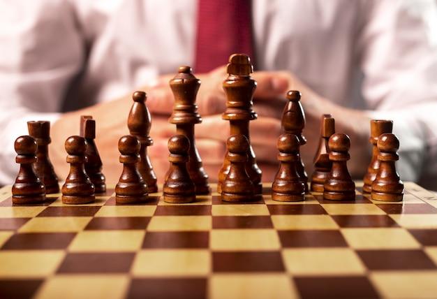 Avvio di attività e concetto di controllo. mani maschii e scacchiera sotto il controllo del capo.
