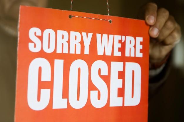 Proprietario del negozio di affari che gira segno chiuso alla porta del negozio