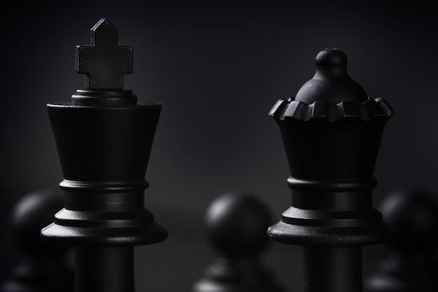 Strategia d'affari. un gioco da tavolo a scacchi. macro figure del re e della regina su uno sfondo scuro. brainstorming.