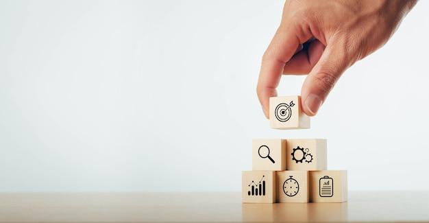 Strategia aziendale che tiene un blocco di legno con finanza aziendale vikon piano d'azione, obiettivi e obiettivi, pile sul tavolo sulla strategia aziendale e piano d'azione.