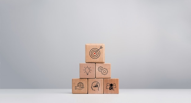 Strategia aziendale con processo di successo di crescita per il concetto di leadership e lavoro di squadra. il piano d'azione, l'icona dell'obiettivo aziendale sui blocchi di legno del cubo impilano la forma piramidale su sfondo bianco.