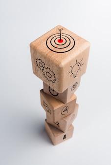 Strategia aziendale con processo di successo di crescita per il concetto di leadership e lavoro di squadra. il piano d'azione, l'icona dell'obiettivo aziendale sulla pila di blocchi di legno del cubo su sfondo bianco, stile verticale.