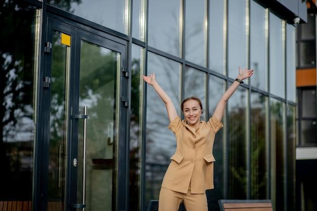 Successo aziendale - felice giovane donna d'affari che celebra i risultati della carriera lavorativa