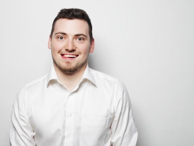 Concetto di affari, successo e persone - giovane uomo d'affari che indossa una camicia bianca, isolato su bianco.