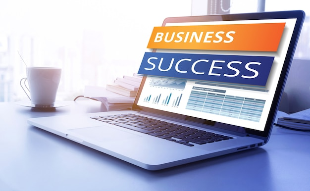 Testo di successo aziendale sullo schermo del laptop con sfondo grafico