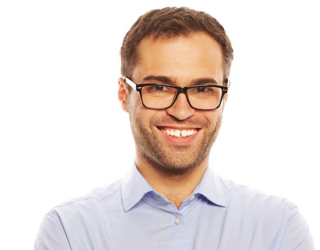 Concetto di affari, successo e persone - bel giovane uomo d'affari in camicia blu che guarda la telecamera in piedi su sfondo bianco