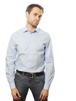 Concetto di affari, successo e persone. bel giovane uomo d'affari in camicia blu guardando la fotocamera in piedi su bianco