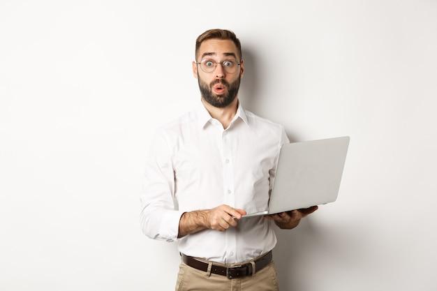 Attività commerciale. uomo d'affari sorpreso che tiene il computer portatile e sembra interessato, in piedi con il computer su sfondo bianco.