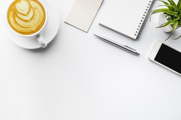 Piano del tavolo aziendale con forniture per ufficio su sfondo bianco.
