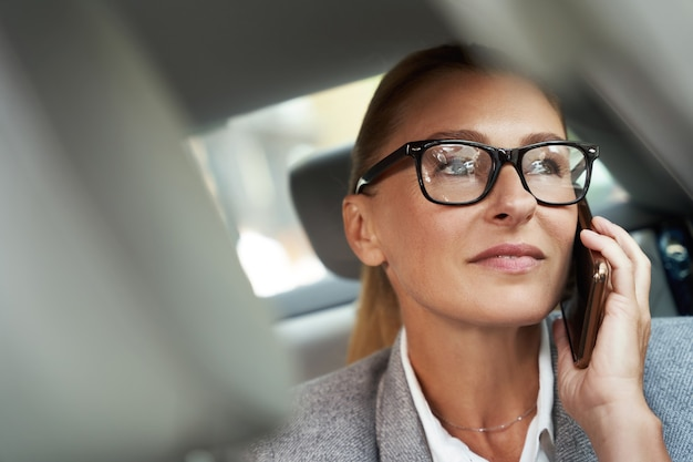 Ritratto di conversazione d'affari di una donna d'affari sicura di successo che indossa occhiali che parla al cellulare