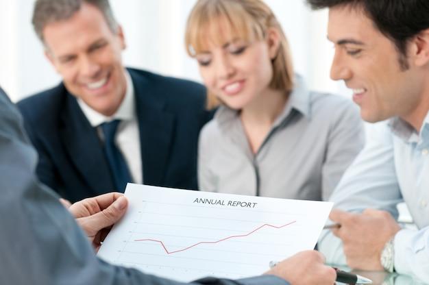 Squadra di affari che analizza insieme la loro relazione annuale positiva alla riunione in ufficio