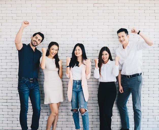 Squadra di affari che celebra un trionfo con le braccia in alto