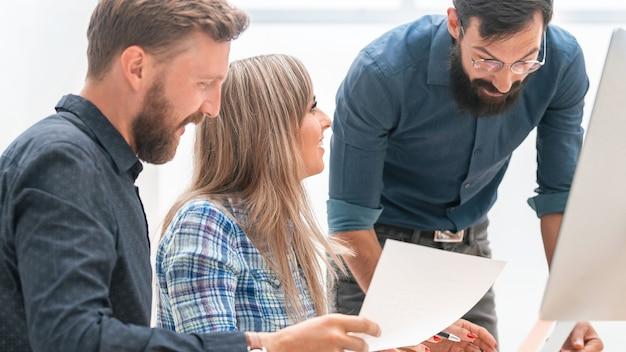 Squadra di affari che discute dei documenti aziendali sul posto di lavoro. il concetto di lavoro di squadra