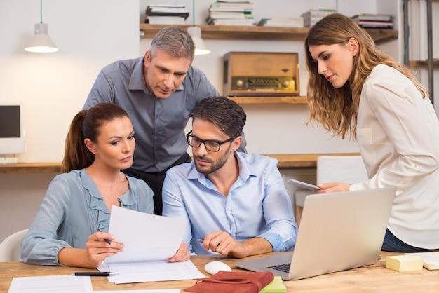 Squadra di affari che discute sul documento e sull'idea alla riunione. persone di affari che esaminano la storia passata di un'azienda per la fusione. incontro in ufficio tra creativi, casual business.