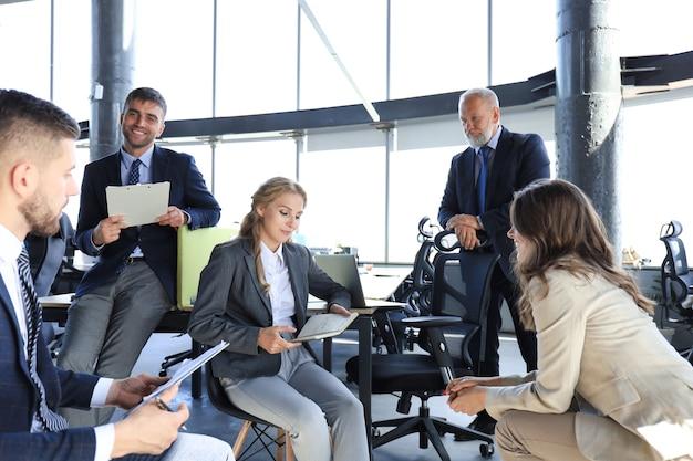 Squadra di affari che discute insieme i piani aziendali in ufficio.