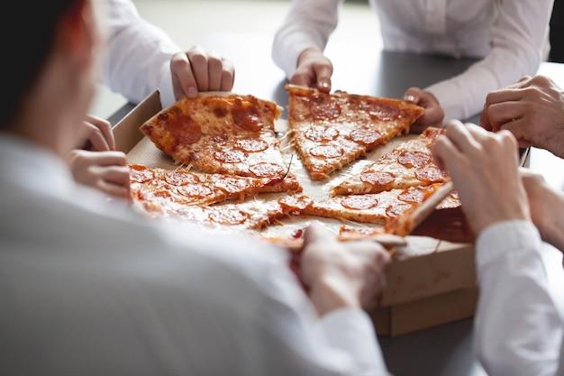 Squadra di affari che mangia pizza in ufficio seduti attorno al tavolo