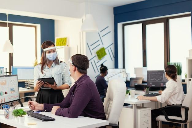 Il team aziendale si aiuta a vicenda per completare una scadenza sul posto di lavoro indossando la maschera facciale durante il covid19. squadra multietnica nel nuovo normale ufficio finanziario in una società aziendale digitando sul computer, senza prendere