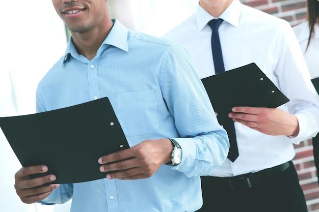 Team aziendale in possesso di una copia del contratto, in piedi in ufficio.