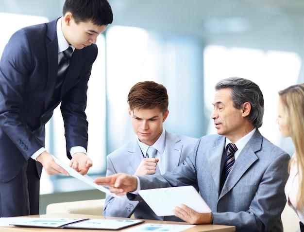 Squadra di affari che intervista giovane richiedente in ufficio luminoso