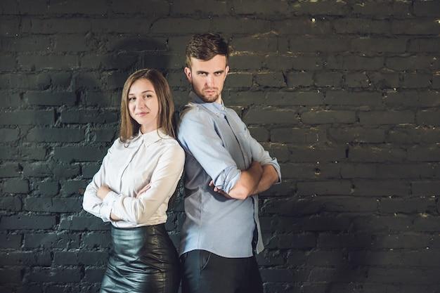 Business team maschio e femmina formato da giovani imprenditori in piedi su una superficie scura.