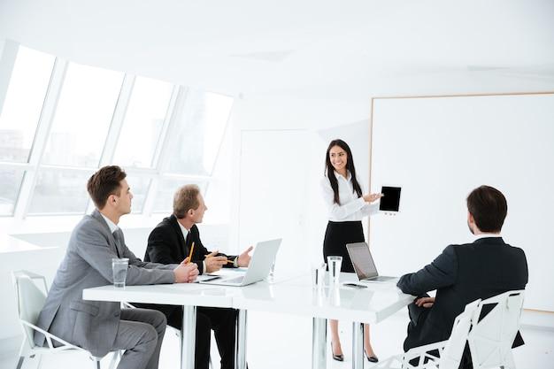 Team aziendale seduto al tavolo in ufficio durante la sessione e donna in piedi vicino al tabellone
