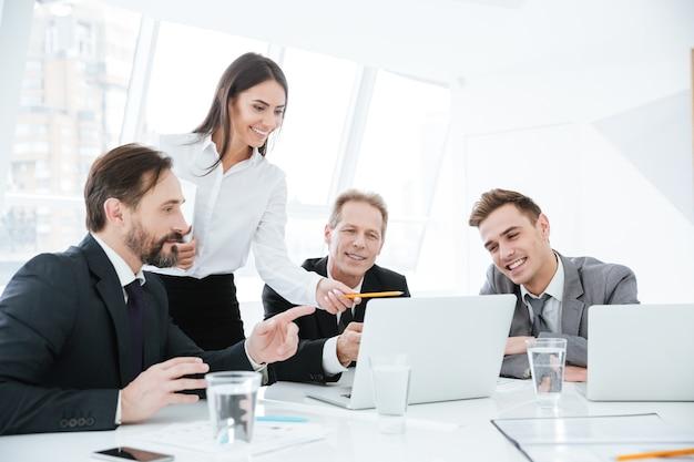 Team aziendale seduto al tavolo con laptop in ufficio