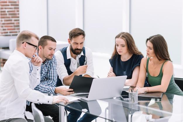 Squadra di affari che si siede allo scrittorio dell'ufficio