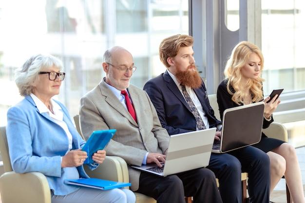 Team aziendale seduto in fila con i laptop che ascoltano la presentazione