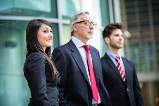 Squadra di affari che sorride all'aperto in un contesto urbano moderno che guarda in avanti