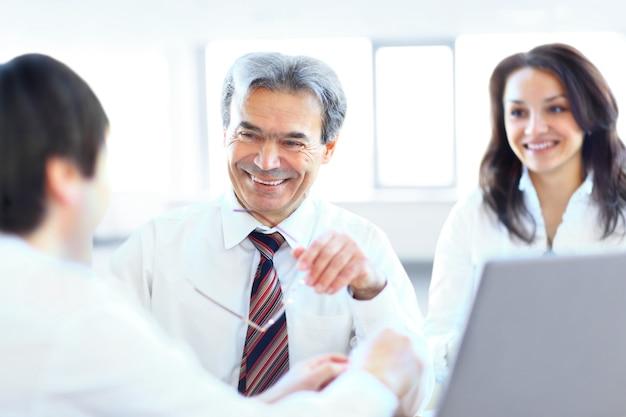 Un team aziendale di tre seduti in ufficio e pianificare il lavoro