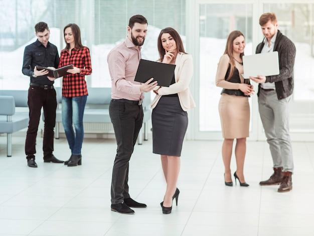Squadra di affari con laptop e documenti in piedi nella hall dell'ufficio prima di una riunione di lavoro