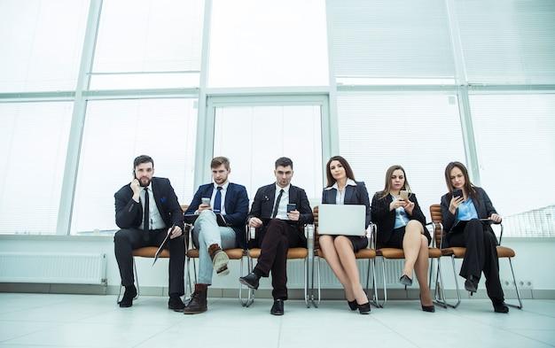 Squadra di affari con smartphone e laptop seduto nella hall dell'ufficio moderno.