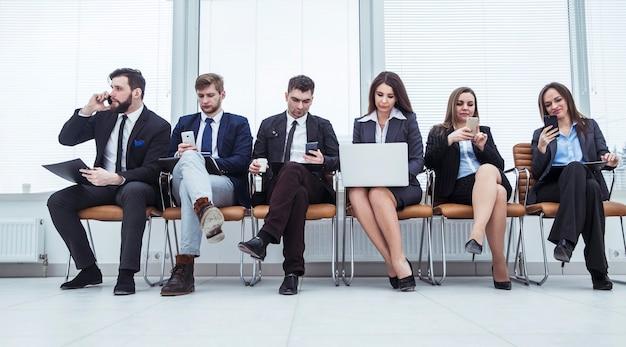 Squadra di affari con smartphone e laptop che si siedono nella hall dell'ufficio moderno.