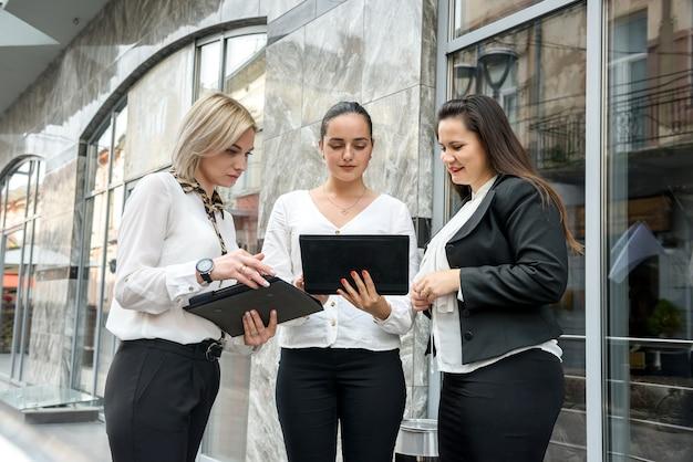 Squadra di affari con le compresse in posa all'esterno dell'edificio per uffici. tre signore che guardano direttamente sullo schermo del tablet