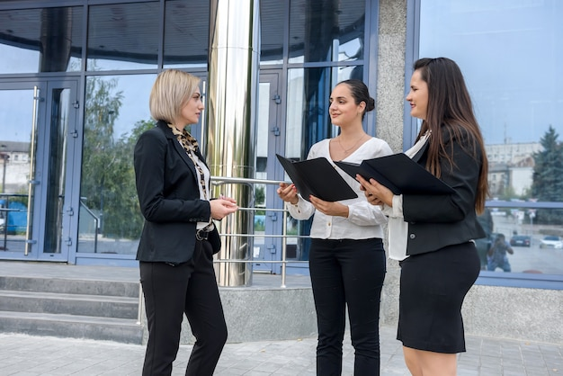 Team aziendale con tablet in posa fuori dall'edificio per uffici