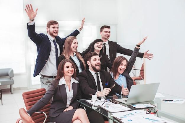 Squadra di affari con le mani alzate e votare per il processo decisionale vicino al desktop