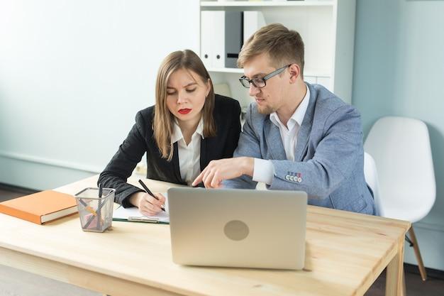 Affari, lavoro di squadra e concetto di persone - uomo serio e donna attraente che lavora al progetto in